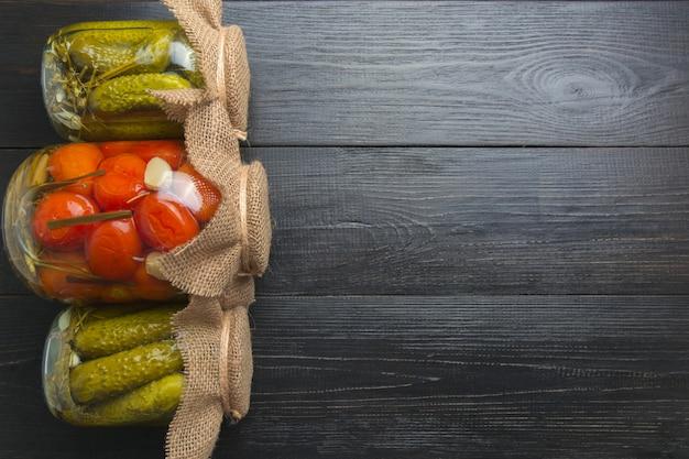 Conservas de legumes pepino e tomate em potes de vidro na placa escura de madeira. vista de cima. preparativos de outono colheita caseira. lição de casa e tradições.