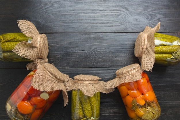 Conservas de legumes pepino e tomate em potes de vidro na placa escura woodeb. vista de cima. vários tipos de conservas. lição de casa e tradições.