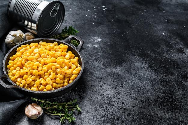Conservas de milho em uma panela. comida enlatada. fundo preto. vista do topo. copie o espaço
