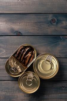 Conservas de peixe enlatado em molho na mesa de madeira escura