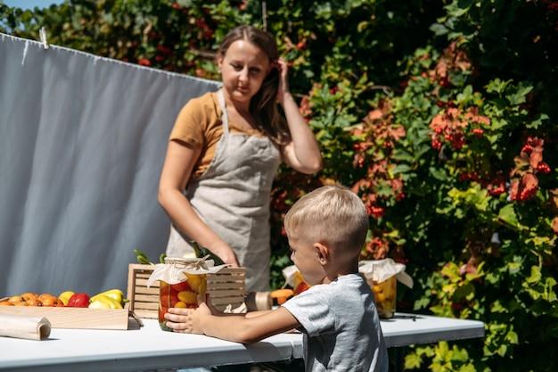 Conservas de vegetais de jardim - preservação de tomates, pimentões, abobrinha, vegetais, mãe e filho em lata