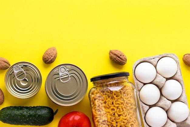 Conservas, nozes, legumes frescos, tomate e pepino, ovos de chichen e macarrão em frasco de vidro no fundo rosa