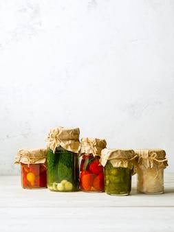 Conservas vegetais nos frascos de vidro no fundo branco. imagem vertical com espaço de cópia