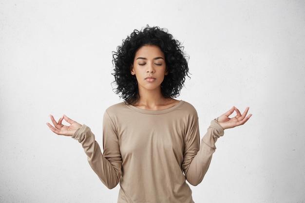 Consideração e oração. calma linda jovem negra com penteado afro, mantendo os olhos fechados enquanto pratica ioga dentro de casa, meditando, de mãos dadas no gesto mudra, pensando em paz