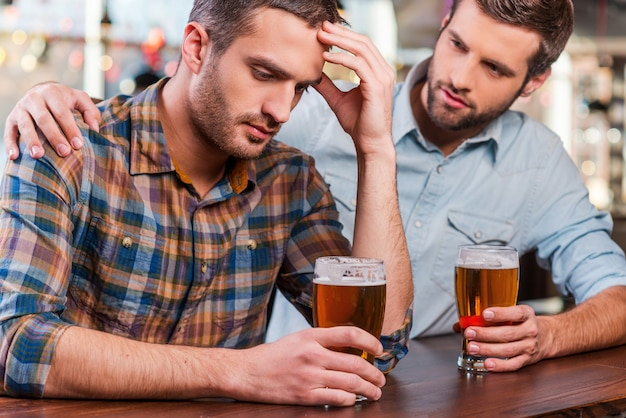 Consolando seu amigo deprimido. jovem deprimido sentado no balcão do bar, segurando a cabeça na mão enquanto é consolado por seu amigo sentado perto dele