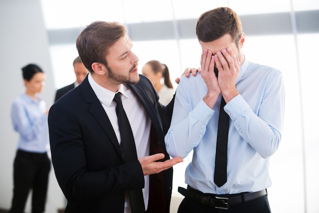 Consolando seu colega desesperado. jovem empresário consolando seu colega deprimido com pessoas em pé ao fundo