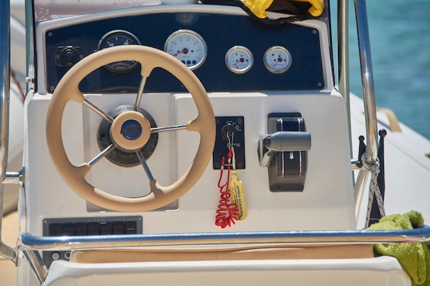 Console de instrumentação a bordo com o leme e acelerador de um grande barco inflável para navegação no mar