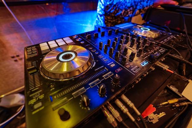 Console de mixagem profissional com discos de vinil para dj está na festa