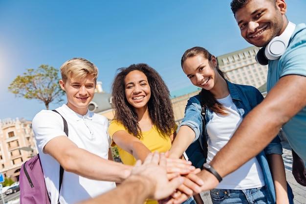 Consolidação de equipe. garotas bonitas com sorrisos nos rostos e tocando as mãos de todos enquanto olham diretamente para a câmera