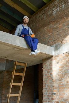 Construa melhor. jovem construtor confiante de macacão azul e capacete olhando para a câmera, sentado no chão de concreto enquanto trabalhava na construção de uma casa