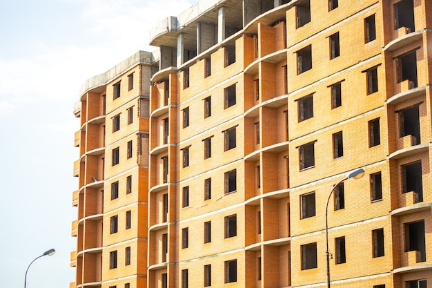 Construção abandonada de um edifício de vários andares, negócio imobiliário ilegal, casa de concreto em fase de revestimento de tijolos