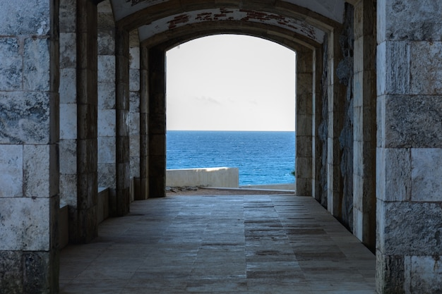 Construção com arco costa rochosa e mar translúcido