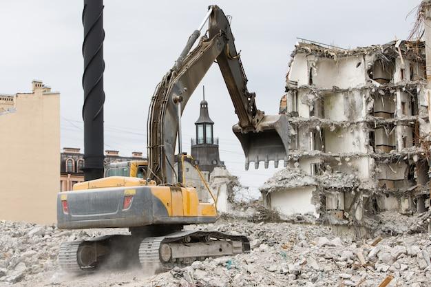 Construção da antiga demolição de hotéis para novas construções, usando uma escavadeira-destruidora hidráulica especial. desmantelamento de casa.