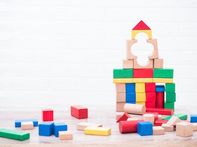 Construção de blocos de madeira por crianças na mesa e tijolos brancos