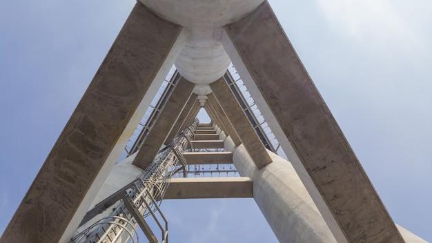 Construção de concreto e escada de metal até o topo com céu azul.