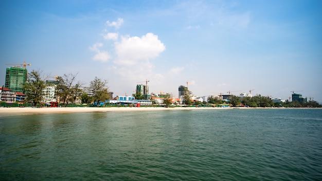 Construção de edifícios de vários andares no camboja, sihanoukville. prédios modernos em construção. praia de areia branca na cidade. muitos guindastes na costa.