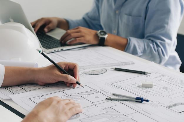 Construção de engenheiro e equipe de interior discutindo no escritório e angineer trabalhando