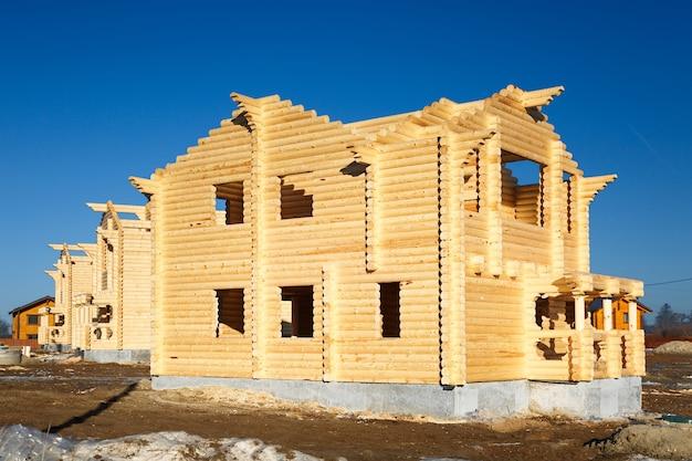 Construção de habitação de madeira, derrubada de um tronco redondo para venda