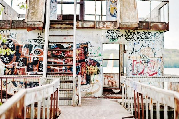 Construção de metal abandonada com escadas e vários desenhos grafite