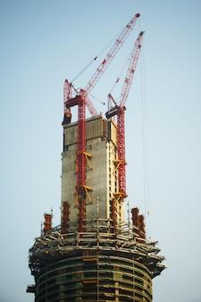 Construção de um arranha-céu por guindastes no dia