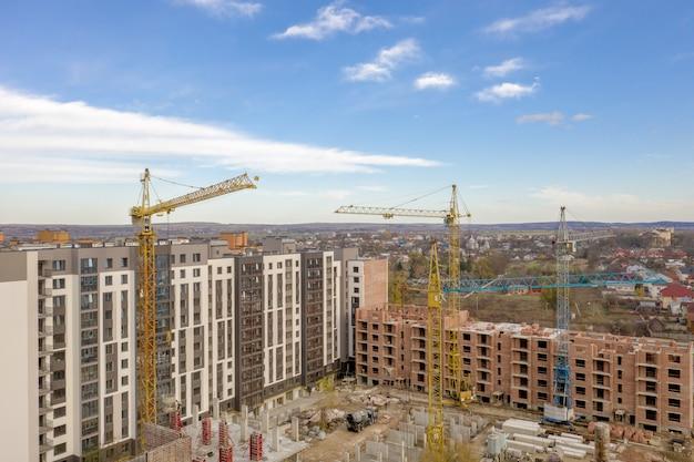 Construção de um novo complexo residencial de vários andares. guindastes e canteiro de obras. prédios modernos estão sendo construídos
