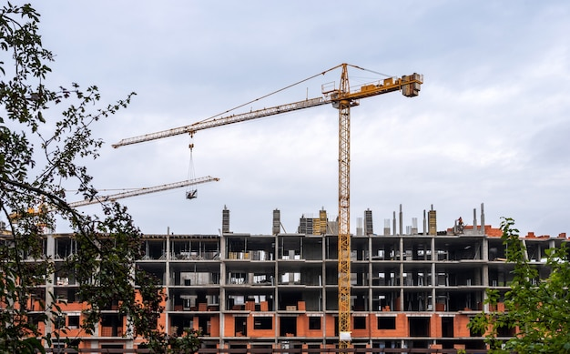 Construção de um prédio de apartamentos em kaliningrado. um guindaste levanta materiais de construção.