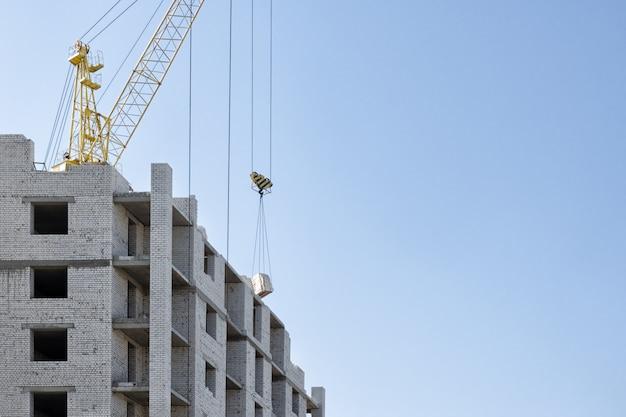 Construção de uma casa de tijolo de vários andares com a ajuda de um guindaste de construção.