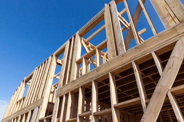 Construção de uma nova casa de madeira de tábuas e vigas de pinho, contra um céu azul, construção privada de uma residência