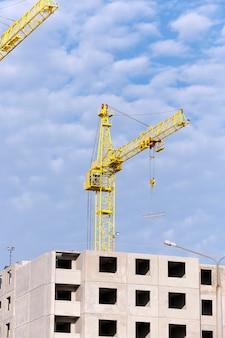 Construção de uma nova casa, guindastes de construção de close-up durante a construção de um novo prédio de apartamentos de vários andares, céu azul,