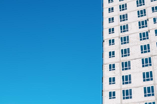 Construção de vários andares inacabada, tijolos brancos, vista externa