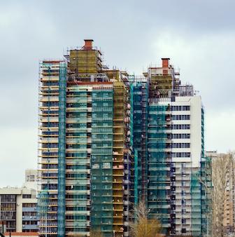 Construção do edifício residencial de vários andares. trabalhos de construção no isolamento do revestimento do edifício.