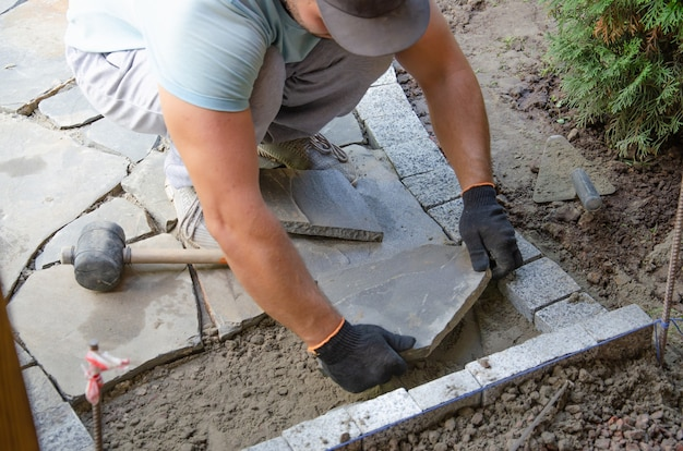 Construção do pavimento perto do pedreiro da casa coloca blocos de pedra de pavimentação de concreto para a construção ...