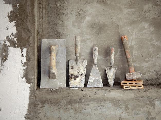 Construção envelhecida argamassa de cimento ferramentas usadas