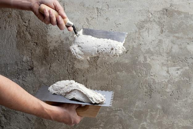 Construção, espátula dentada e trabalhador mãos