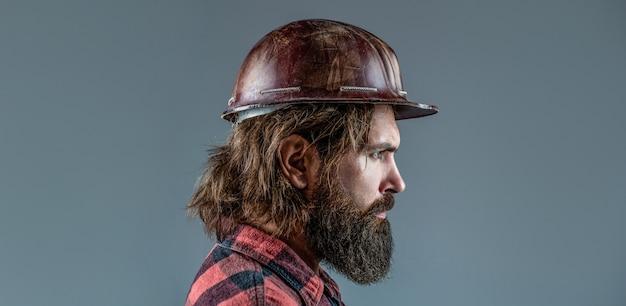 Construção, indústria, conceito de construtor de tecnologia. trabalhador de homem barbudo com barba na construção de capacete ou capacete. construtores de homem, indústria.
