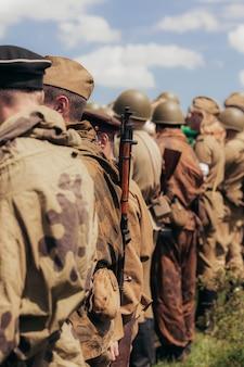 Construção militar de soldados durante a reconstrução das hostilidades em maio, uma área estreita de nitidez, foco no rifle. foto de alta qualidade