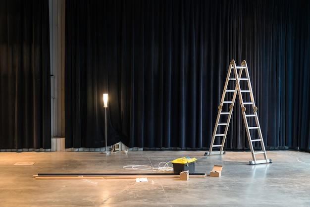Construção no edifício da fábrica ou no interior do armazém. escada, reparando ferramentas.
