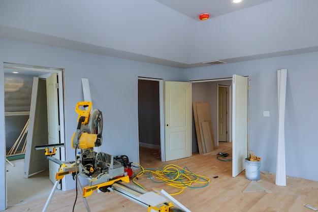 Construção que remodela em casa o corte da placa de madeira da guarnição sobre com a serra circular.