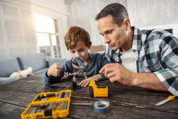 Construindo. bonito homem concentrado e amoroso de cabelos escuros mostrando instrumentos para seu filho enquanto está sentado à mesa e olhando para uma lupa