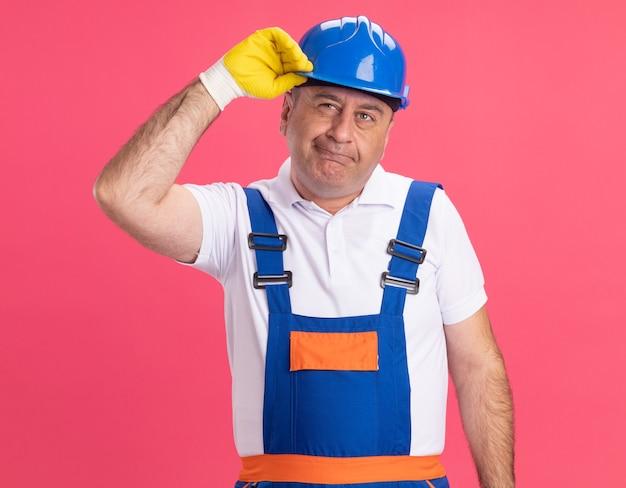 Construtor adulto atencioso, de uniforme, usando luvas de proteção, segurando um capacete de segurança isolado na parede rosa