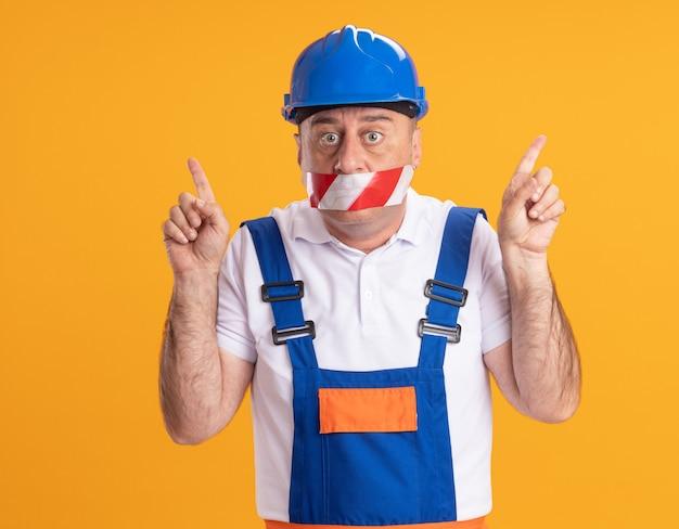 Construtor adulto, caucasiano, chocado, de uniforme cobre a boca com fita adesiva apontando para cima com as duas mãos em laranja