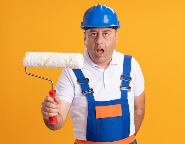 Construtor adulto, caucasiano, chocado, de uniforme, segurando uma escova giratória em laranja