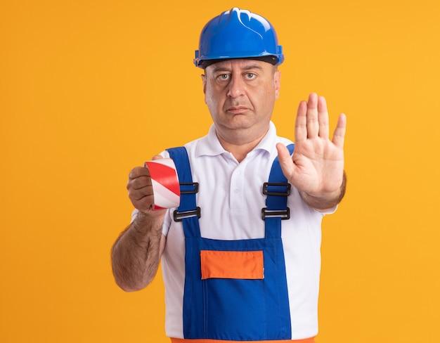 Construtor adulto, caucasiano, confiante, de uniforme, segurando fita adesiva e fazendo gestos para parar o sinal com a mão na cor laranja