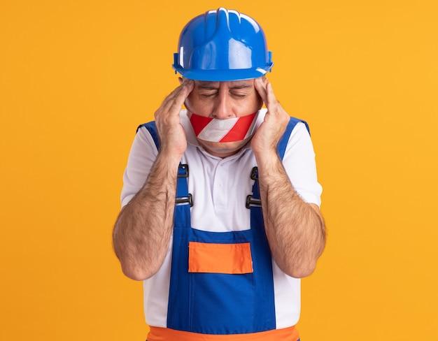 Construtor adulto, caucasiano, dolorido, de uniforme, cobriu a boca com fita adesiva e colocou as mãos nas têmporas em laranja