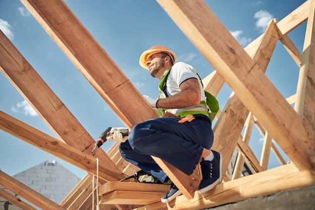 Construtor alegre olhando para o céu azul enquanto faz uma pausa durante o trabalho duro