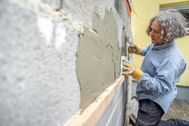 Construtor aplicando ladrilhos a uma parede com cimento de ladrilho em um conceito arquitetônico, de renovação, diy ou novo de construção, perspectiva de ângulo oblíquo.