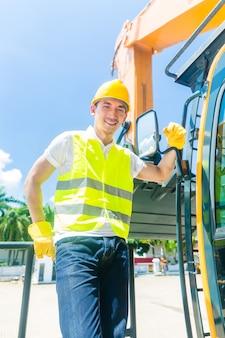Construtor asiático com escavadeira no canteiro de obras