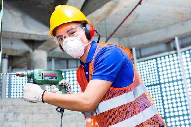 Construtor asiático indonésio ou trabalhador de canteiro de obras perfurando com uma máquina ou furadeira, proteção para os ouvidos, máscara e capacete ou capacete em uma parede de um edifício de torre