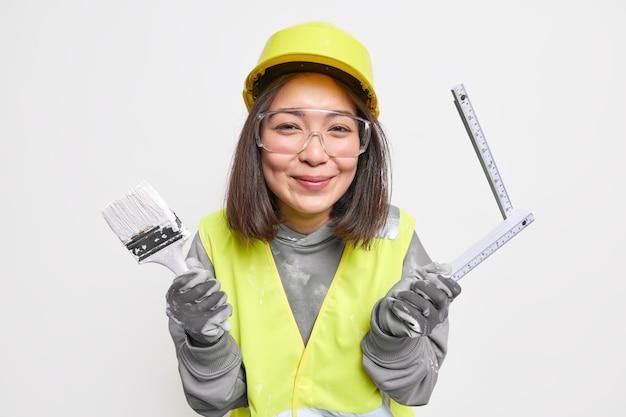 Construtor asiático satisfeito segurando pincel e fita métrica usa capacete de proteção, óculos e luvas vestindo poses de uniforme de trabalho com ferramentas de construção