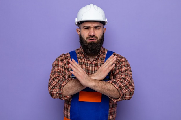 Construtor barbudo com uniforme de construção e capacete de segurança olhando para a câmera com uma cara séria, fazendo gesto de parada, cruzando as mãos em pé sobre o fundo roxo
